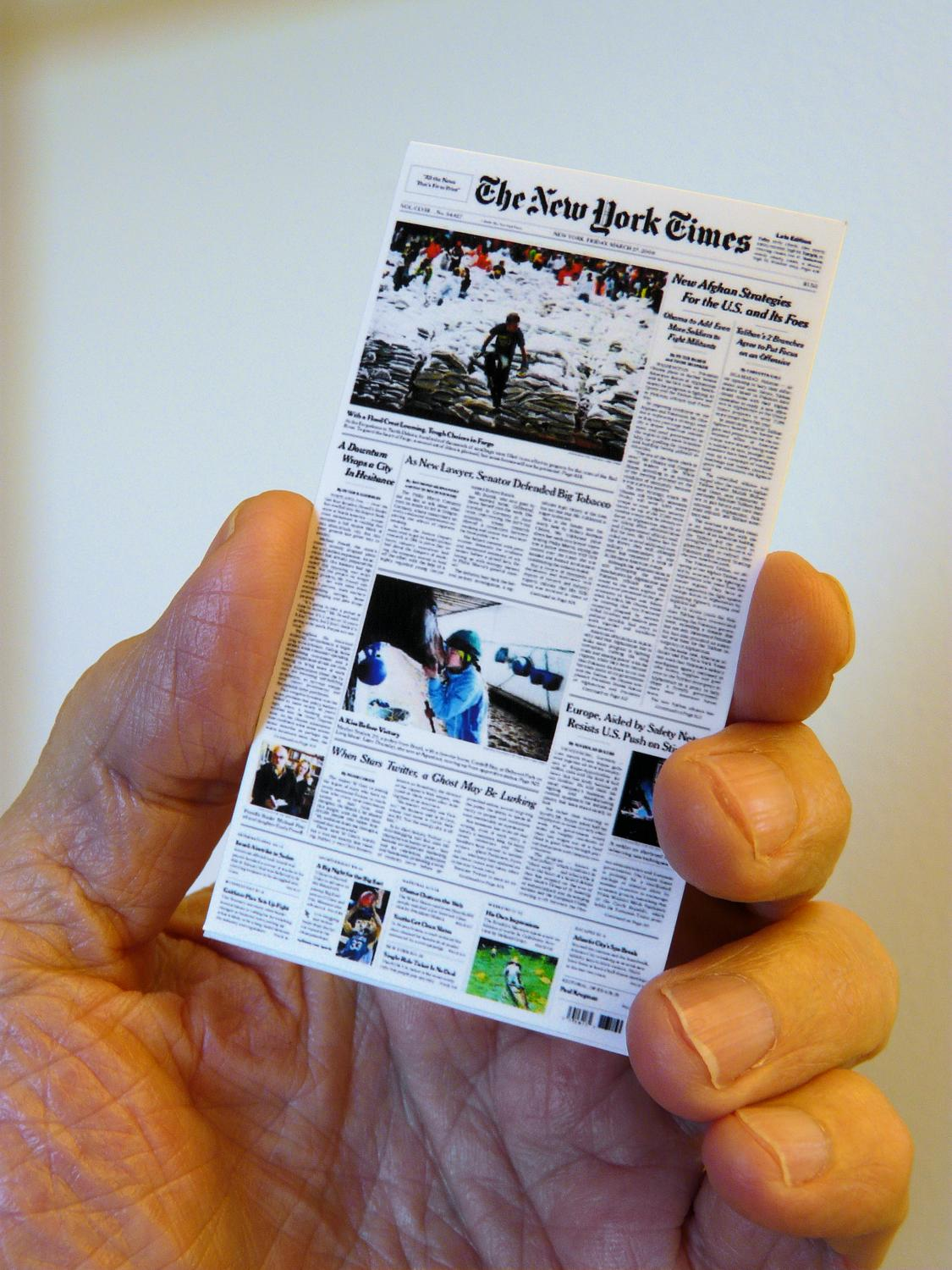 Hand holding nano edition of the NY Times - The