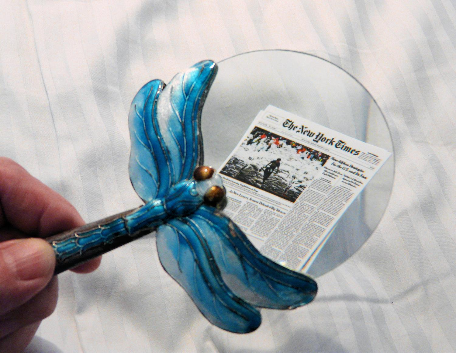 Dragonfly magnifier examining nano edition of the New York Times - Subscribers to the Nano edition will get this