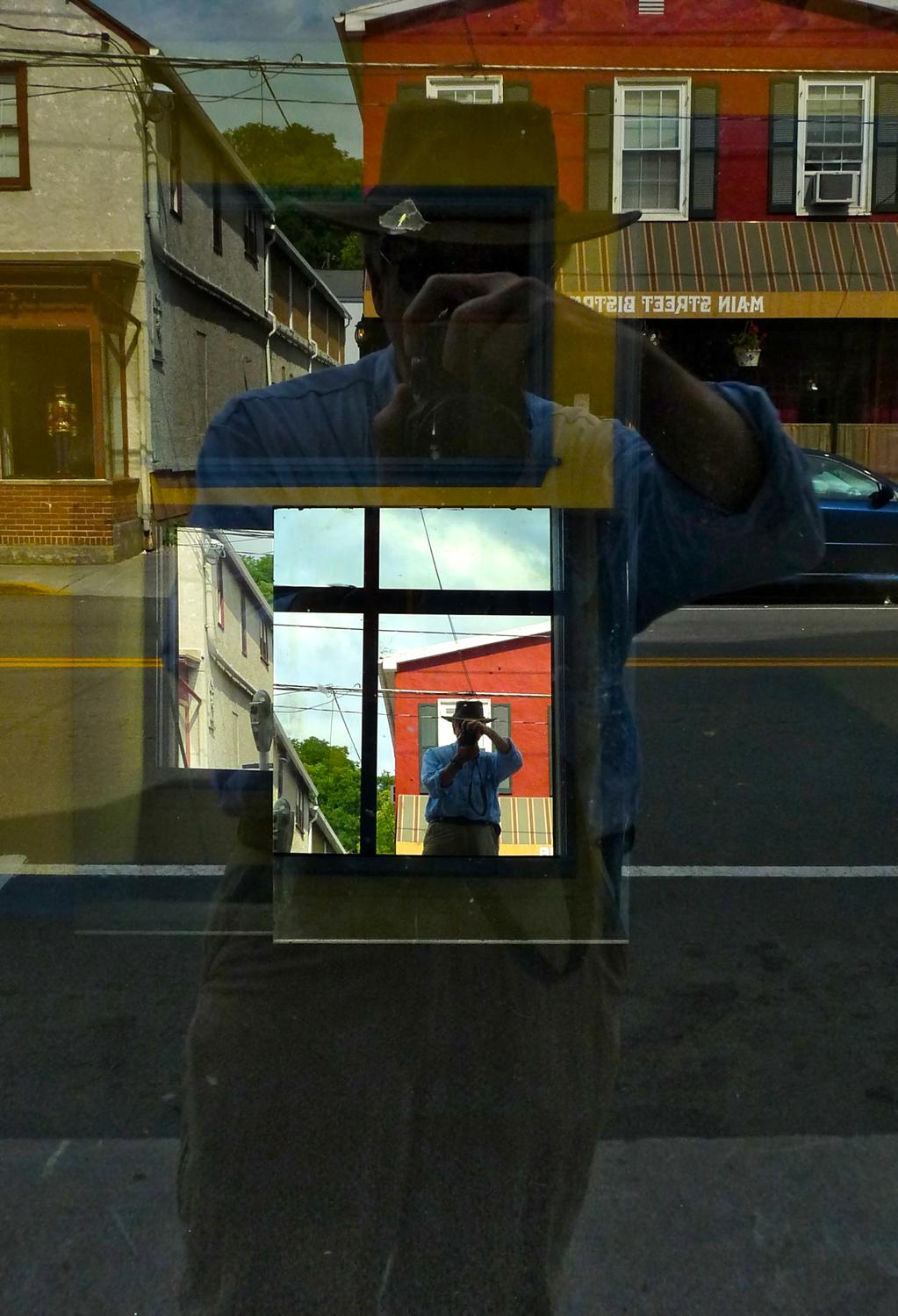 a reflection of the artist in a mirror in a store window - The spirit of René Magritte visits Berryville - Berryville Virginia - Panasonic DMC-FZ28 - - art  - photography - by Tony Karp